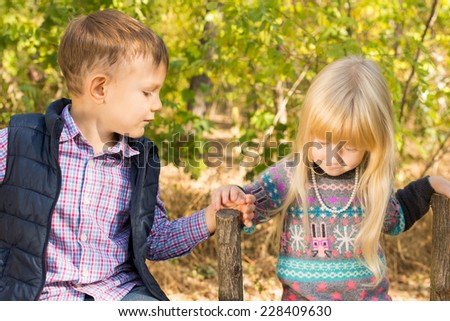 First love - little sweethearts with a cuter little blond girl tenderly taking the hand of a handsome little boy as they stand together outdoors in the countryside