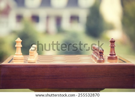 First move over a wood chessboard. Closeup chess game figures isolated outside home background. Real estate sale, home savings, loans market, mortgage plan and residential tax saving strategy concept - stock photo