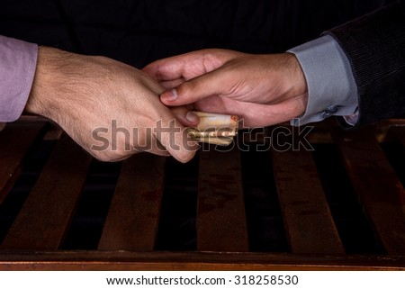First person is giving 50000 Rupees Pakistani Currency Notes to another Person under the table .