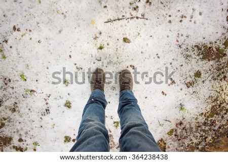 First person view of foot with boots on the snow - stock photo