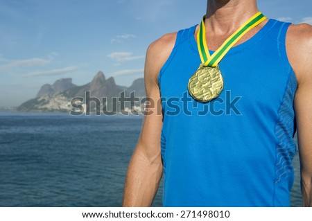 First place athlete wearing gold medal standing outdoors at Ipanema Beach Rio de Janeiro Brazil  - stock photo