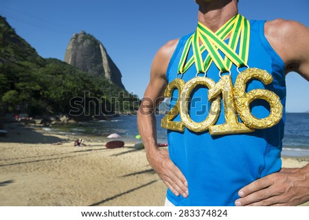 First place 2016 athlete wearing gold medals standing outdoors in front of Sugarloaf Mountain Rio de Janeiro Brazil  - stock photo