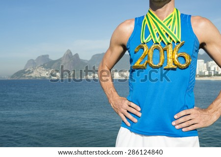 First place athlete wearing 2016 gold medals standing outdoors on Ipanema Beach Rio de Janeiro Brazil  - stock photo