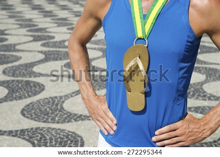 First place Brazilian athlete standing with flip flop gold medal at the Copacabana Beach sidewalk in Rio de Janeiro Brazil - stock photo