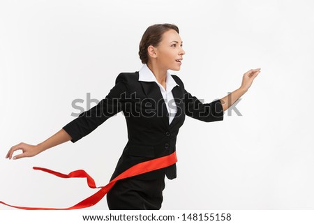 First place in business. Beautiful young businesswomen passing finishing line while isolated on white - stock photo