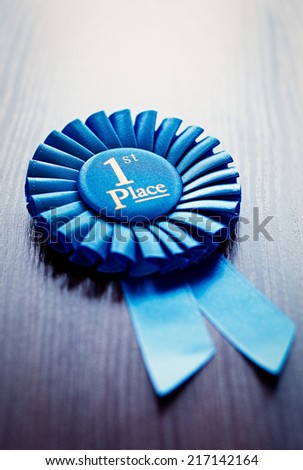 First place winners rosette or badge in pleated blue ribbon with central text to be awarded as a prize in a competition, race, or sport at an oblique angle on grey with copyspace - stock photo