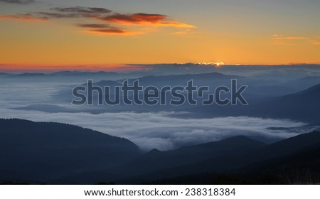 First rays of sunrise over foggy mountains - stock photo