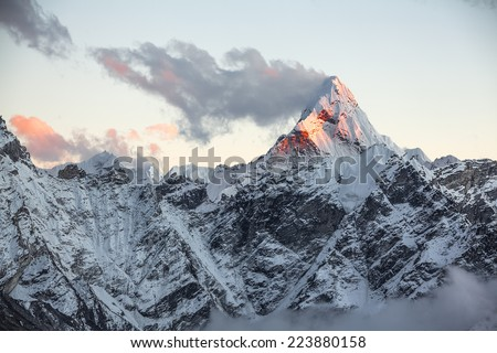 First rays of the rising sun on the top of sacred Ama Dablam peak (6814 m). Nepal, Himalayas. Canon5D MkII. - stock photo
