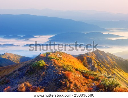 First rays of the sun on the mountain slopes. Panoramic landscape of the ridge with a footpath - stock photo