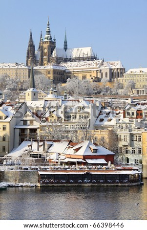 First Snow in Prague, gothic Castle above the River Vltava in the sunny Day