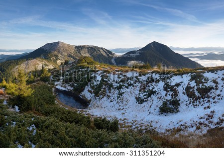First snow in the mountains. Autumn landscape with a mountain lake. Carpathians, Ukraine, Europe