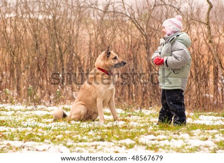 First snow. Little girl playing with her dog. - stock photo