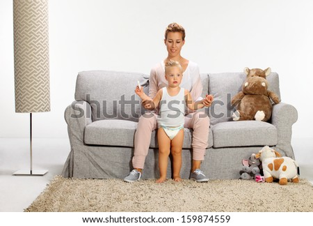 first step, Mother and baby daughter playing in living room