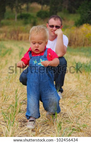 first steps. beautiful funny girl on the meadow - stock photo