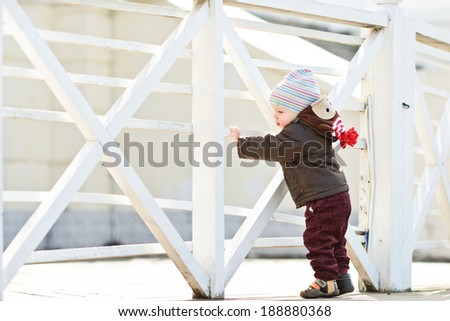 first steps of baby boy near the fence - stock photo