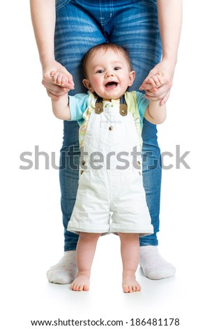 First steps of baby boy with help of mothers hands - stock photo