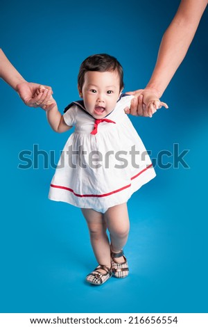 First steps of baby isolated on blue background. Baby Walking with Dad and Mom - stock photo