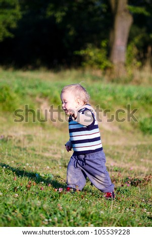First steps of baby on nature background