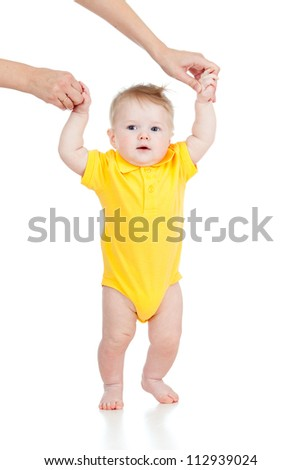First steps of baby with help of mothers hands - stock photo