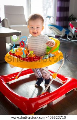 First steps of by little boy in the baby walker  - stock photo