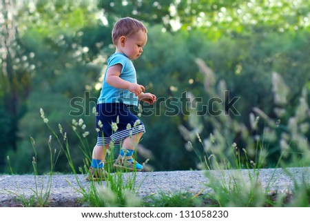 first steps of cute baby boy on footpath among greens - stock photo