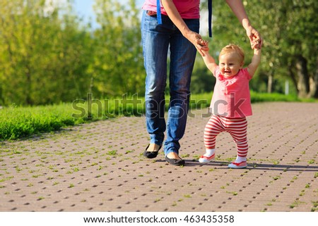first steps of little girl in summer nature