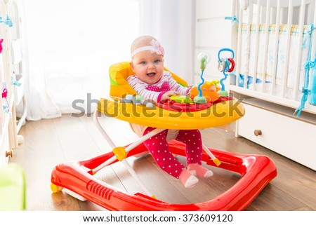 First steps of the girl in a baby walker - stock photo