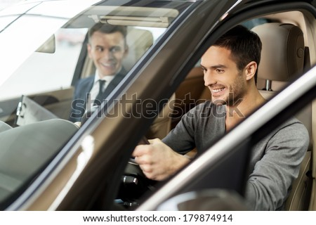 First test drive. Handsome young man ready to make first test drive - stock photo
