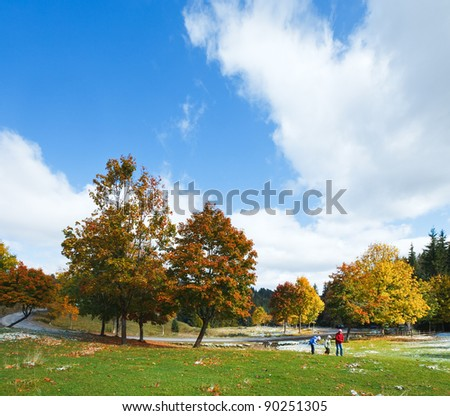 First winter snow and autumn colorful foliage near mountain secondary road (and mother with children) (Carpathian, Ukraine) - stock photo