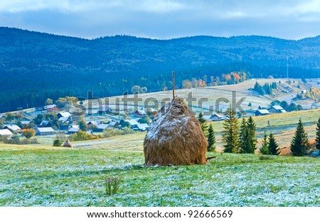 First winter snow on October Carpathian mountain plateau with village and highway far away - stock photo