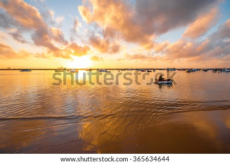 Fiserman with boat in the ocean near the sandy beach on the sunrise