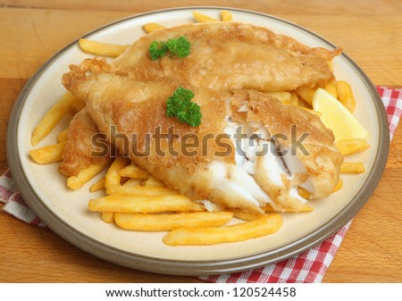 Fish and chips. Battered and deep fried cod fillet with fries. - stock photo