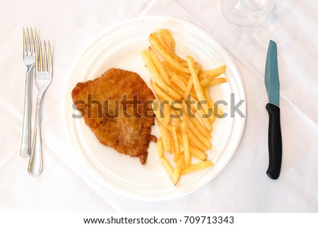 fish and chips. fried fish and potatoes chips in ceramic white dish, stainless utensils, top view.