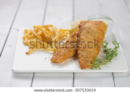 Fish and chips. Fried fish fillet with french fries wrapped by paper cone, on wooden background. Fresh cooked with hot smoke. - stock photo