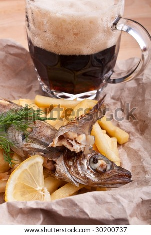 fish and chips in a piece of brown craft paper and a glass of beer - stock photo