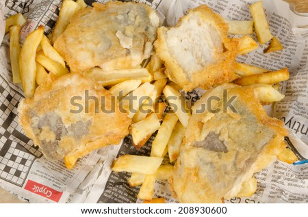 Fish and chips on their traditional newspaper wrap - stock photo