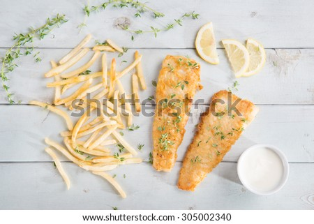 Fish and chips. Top view fried fish fillet with french fries on wooden background. - stock photo