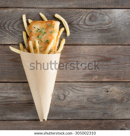 Fish and chips. Top view fried fish fillet with french fries wrapped by paper cone, on wooden background. - stock photo