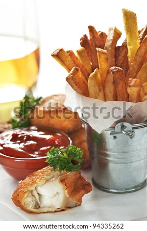 Fish and chips with ketchup on paper wrapping - stock photo