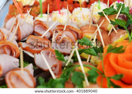 fish and meat snack with vegetables on  chopsticks - stock photo