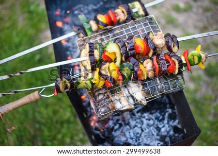 Fish and pickled vegetables on the charcoal grill together. Home barbecue picnic. - stock photo