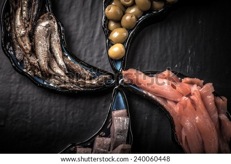 Fish assortment and olives on magic plates on a dark background