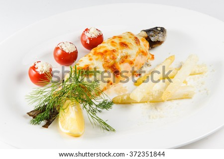Fish baked under cheese with vegetables on a plate - stock photo