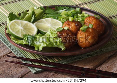 fish balls in curry sauce with lime and fresh herbs and chopsticks on a bamboo table close-up. horizontal  - stock photo