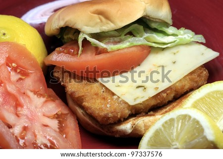 Fish burger seafood sandwich on bun with cheese, lettuce and tomatoes.