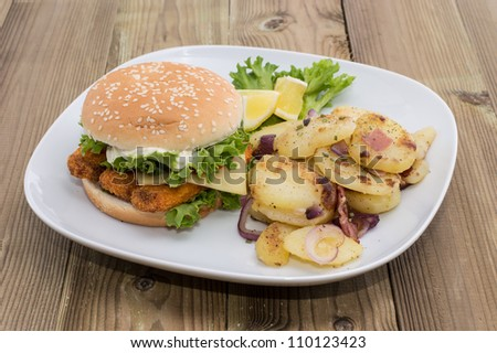 Fish Burger with fried Potatoes on wooden background