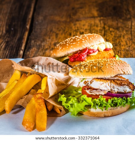 Fish burger with rustic chips on white paper for takeaway