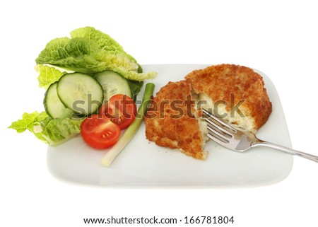 Fish cake and salad with a fork on a plate isolated against white