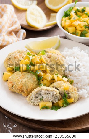 fish cakes with mango salsa and rice, vertical, close-up - stock photo
