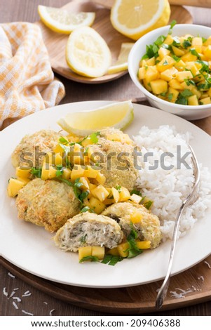 fish cakes with mango salsa and white rice, vertical - stock photo